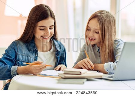 Pleasant cooperation. Upbeat teenage girls sitting at the table and doing their home assignment, helping each other with it while smiling