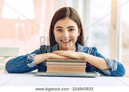 Love learning. Pretty upbeat teenage girl sitting at the table and resting her hands on a pile of study materials while posing for the camera