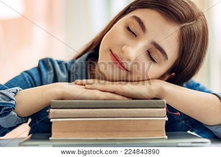 Necessary rest. The close up of a petite teenage girl sitting at the table and taking a nap, resting her head on the arms folded on a pile of books