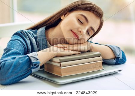 Tired after studying. Adorable teenage girl sitting at the table and taking a nap on a pile of books serving her as a pillow, being tired after studying
