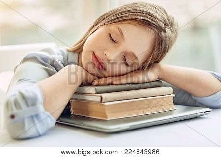 Sweet rest. Charming teenage girl taking a nap while sitting at the table and resting her head on the hands folded on a pile of books
