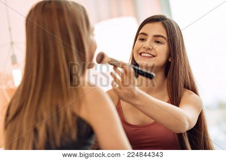 Taking good care. Pleasant upbeat girl applying the powder to the face of her younger sister, using a brush for it, while smiling at her fondly