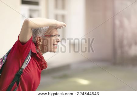 Happy senior woman looking ahead with her hand at her forehead, excited to leave home and go on a trip