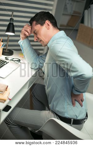 Horrible pain. Top view of painful young male employee sitting at the office while puckering and putting hands on head and back