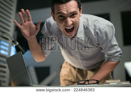 Aggressive behavior. Young uncontrolled male employee yelling while leaning on table and waving hand