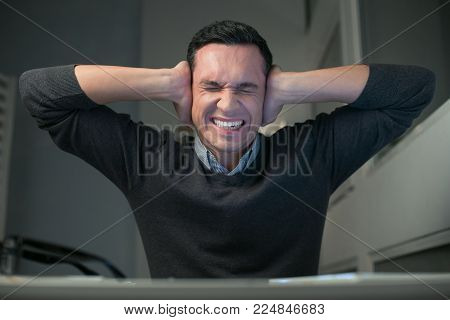Nervous situation. Angry exhausted pretty man putting hands on the ears while clenching teeth and closing eyes