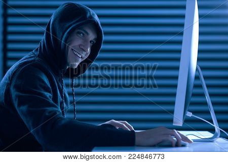 My congratulations. Pleased merry male gamer looking at the camera while sitting in front of computer and smiling