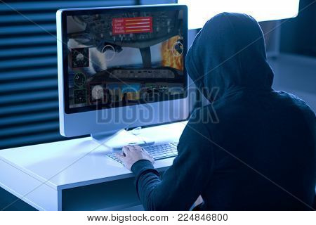 Die enemy. Professional focused male gamer sitting at the table while playing game and putting hand on the keyboard