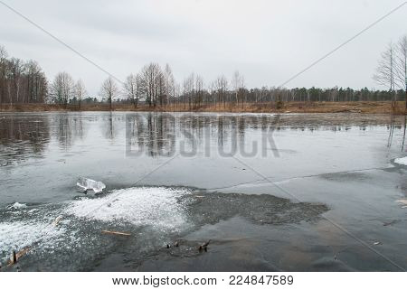 cracked ice on the pond in the spring, the danger during the flood, early spring in Belarus