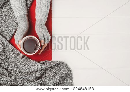 Female hand holding a cup of tea or coffee on white wooden table. Winter or christmas cosy background. Photograph taken from above, top view with copy space