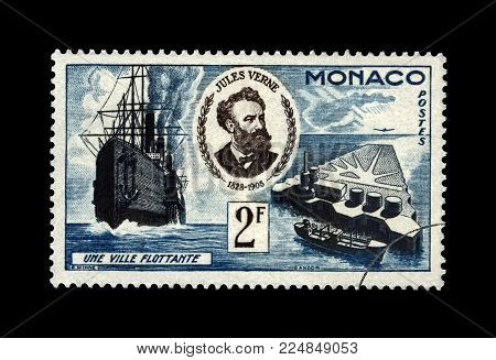 MONACO - CIRCA 1955: canceled postal stamp printed in Monaco shows Jules Verne, famous science writer and Floating City, circa 1955. Vintage stamp isolated on black background.