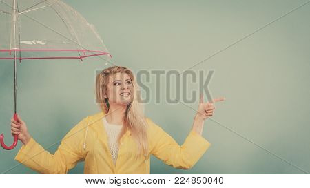 Blonde woman wearing yellow raincoat holding transparent umbrella checking weather if it is raining pointing with finger at copyspace.