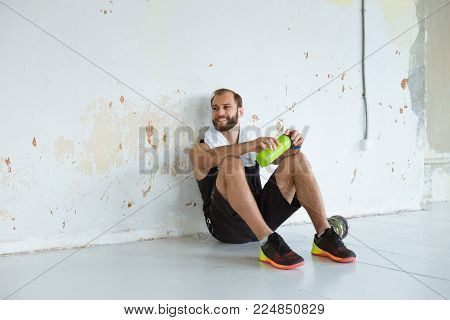 Fit man taking a break from working out at the gym and drinking water. Smilling.