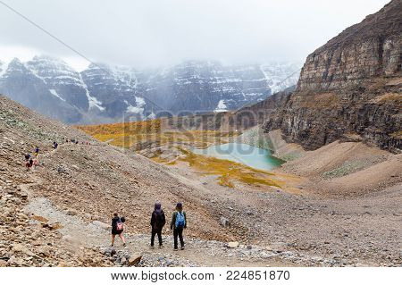 LAKE LOUISE, CANADA - SEPT 17, 2016: Hikers traverse the rocky trail at Sentinel Pass in the Larch Valley near Lake Louise in Banff National Park, Alberta, with snow-capped Valley of Ten Peaks in the background and Minnestimma Lakes in the valley.