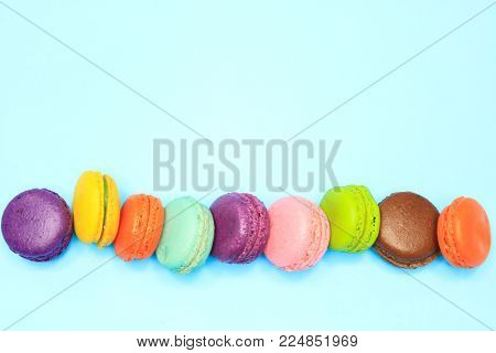 Macaroons put in a row, macaroons on blue background