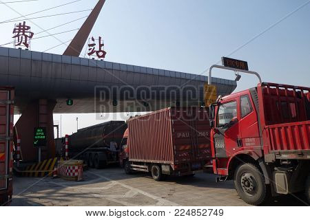 SHANGHAI, CHINA-JAN 08, 2018:  Trucks line up at the toll both of a highway in Shanghai, China.