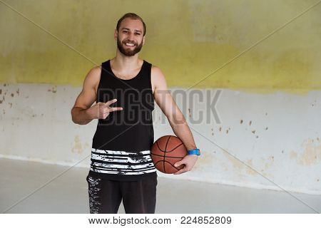 a young basketball player is smilling and holding a ball in his hand.