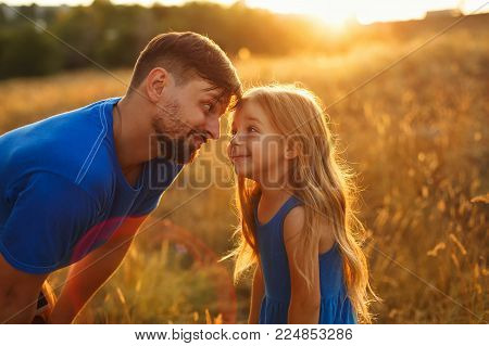 Family values. Father and daughter look into each other's eyes. They are walking in the field at sunset. The joy of fatherhood. Solar glare
