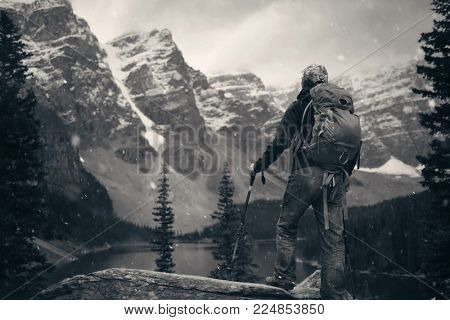 Hiker in Moraine Lake with snow capped mountain of Banff National Park in Canada in a snowing day