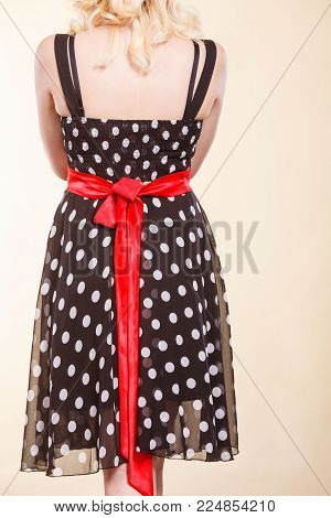 Retro, pin up, elegant and timeless clothes concept. Woman wearing retro dotted black dress with big red bow