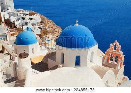Santorini skyline with blue dome church and buildings in Greece.