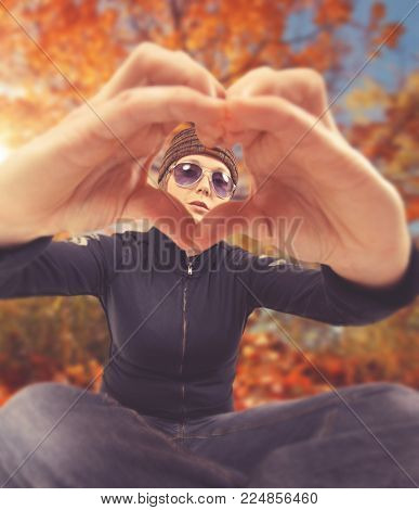 cute girl holding her hands in a heart shape in front of a pretty autumn tree toned with a retro vintage instagram filter