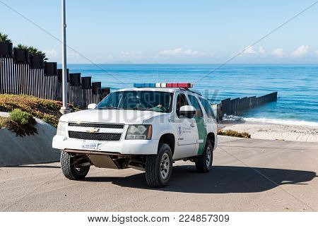 SAN DIEGO, CALIFORNIA - NOVEMBER 4, 2017:  A Border Patrol vehicle patrols the international border wall near the ocean at Border Field State Park, the southwesternmost beach in the United States.