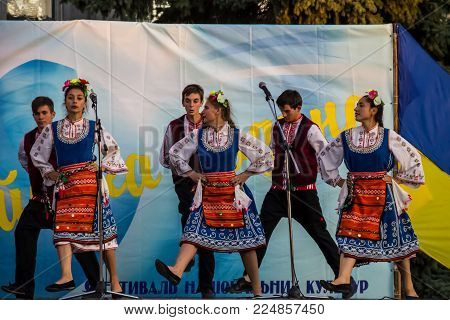Genichesk, Ukraine - August 26, 2017: Dancers in bulgarian traditional clothing performs on stage during Festival of National Cultures Tavriyska rodyna (Tavria Family)