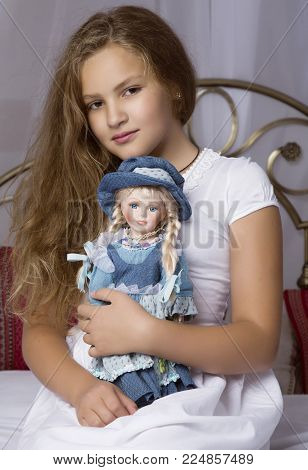 beautiful little girl sitting on a bed and hug her baby doll