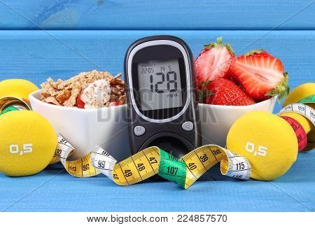 Glucose meter with result of measurement sugar level, healthy food, dumbbells for fitness and centimeter, concept of diabetes and healthy nutrition