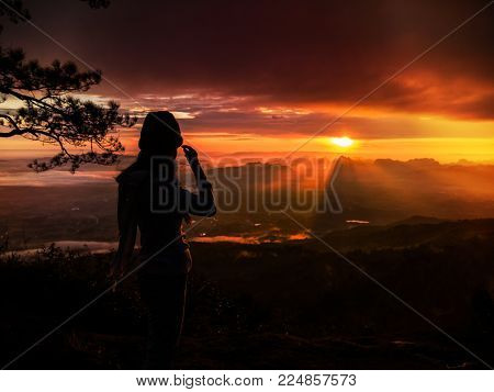 silhouette Alone woman Standing Live on the mountain In the midst of nature While the sun is rising. In the morning the sun shines.