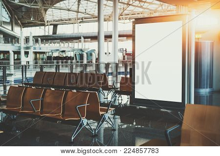 Blank white billboard placeholder mockup in shopping mall; empty informational banner in airport waiting hall or waiting room of railway station depot surrounded by rows of empty wooden seats