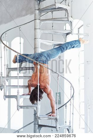 A man in denim jeans upside down on iron ladder.