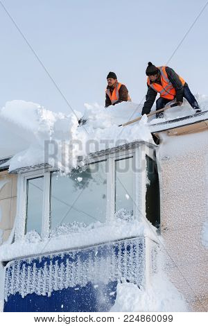 PETROPAVLOVSK CITY, KAMCHATKA PENINSULA, RUSSIA - DEC 27, 2017: Workers in orange vests with snow shovels cleaning snow drifts from roof of high-rise building after bad weather (snowstorms, blizzard)
