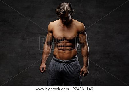 Studio portrait of shirtless muscular male isolated with contrast illumination on grey background.