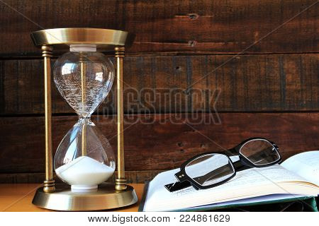 A Time-out Sand glass with Book and Eyeglasses