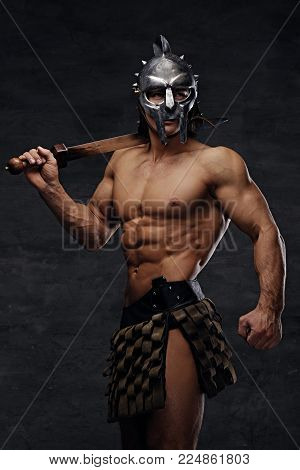 Brutal shirtless muscular male in a silver gladiator helmet holds an iron sword on his shoulder.