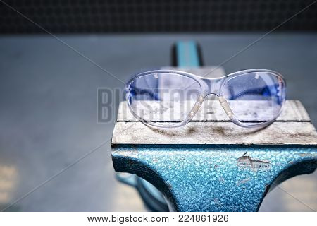 Protective glasses. Safety precautions. The glasses lie on a vise.