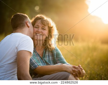 Son kissing her affectionate mother, sunset background.