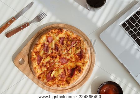 Tasty pizza on office desk with coca and laptop, fast food