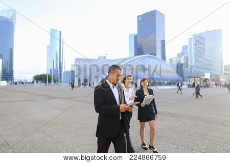 Business person from back walking outside with blue document case in  . Concept of successful female employee and biz. Young woman has short blonde hair and wears black suit.