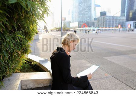 Businesswoman talking with partner by smartphone outdoors and keeping blue document case. Concept of modern technology and cheap tariff plan. Gladden woman has hair blonde hair and wears black suit.