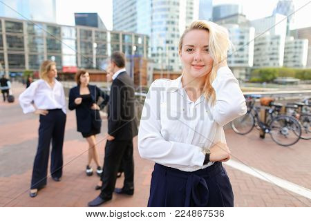 Blonde secretary looking at camera and playing with hair near talking employees background. Concept of businessperson and La Defense Paris. Young blonde woman is beautiful.