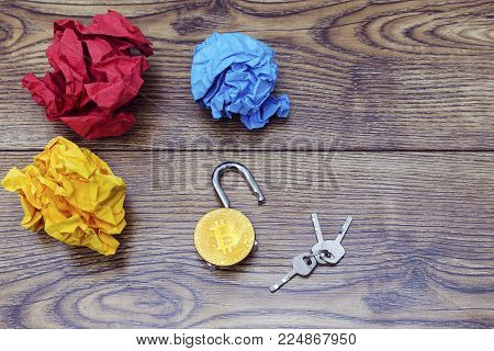 crumled paper balls, keys, chain and bitcoin on wood.