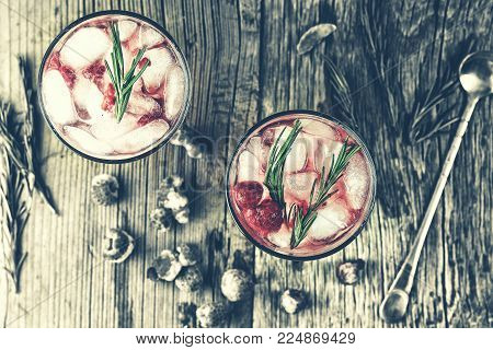 Alcoholic Cocktail. Fruity cocktail drink with the addition of alcohol is decorated with frozen or fresh raspberry, strawberry, rosemary, ice and soda. Domestic cocktail with ice and rosemary