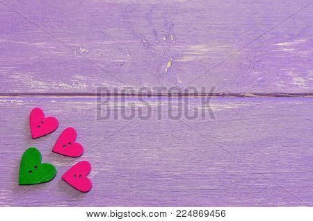 Heart shaped buttons. Wooden buttons on a purple wooden background. Valentines day buttons set. Top view