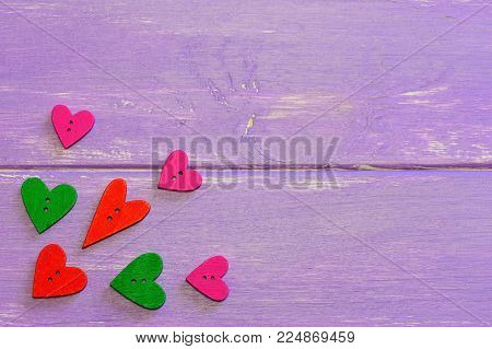 Colorful heart shaped buttons. Love heart wooden buttons in various colors. Purple wooden background with copy space for text. Valentines buttons. Top view