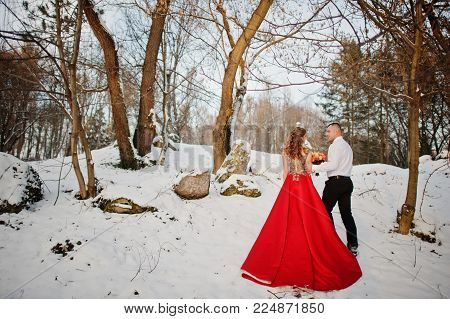 Amazing Couple In Winter Fairytale Forest In Love. Girl In Red Beautiful Dress. Valentine's Day Them