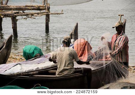Kochi, India - 11 January 2018: Fishermen On Fishing Boat Checking Net In Fort Kochi Beach In Kerala