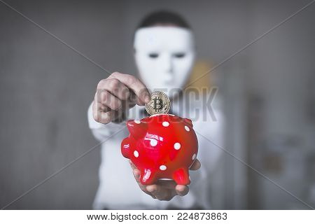 Unknown person in white mask drop bitcoin into piggy bank